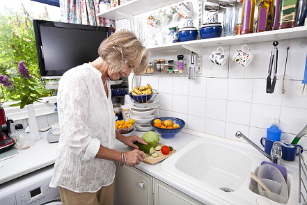 A woman prepares food in her kitchen